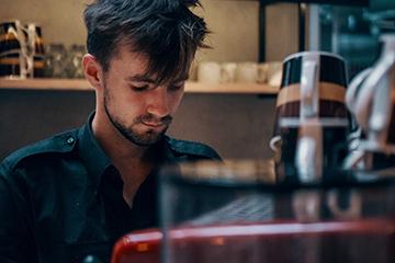 Restaurateur servant un café dans son restaurant après avoir créé sa société